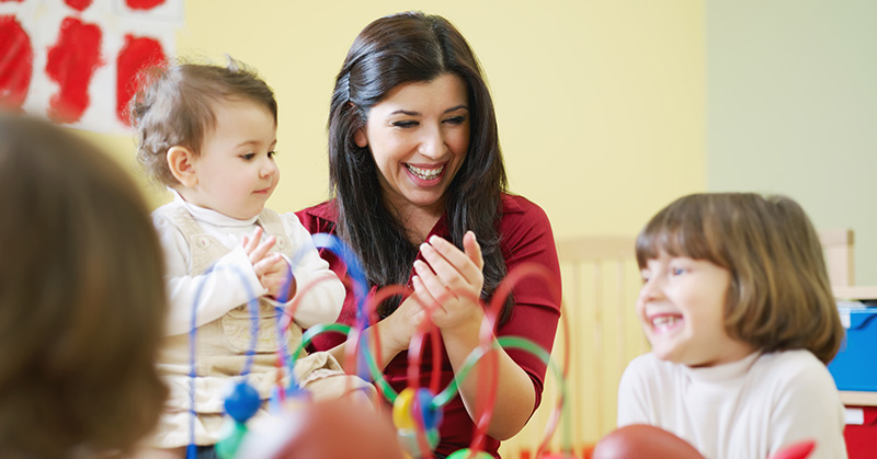 Woman playing with smiling children
